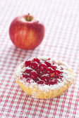 Beautiful cake with berries and apple on plaid fabric — Stock Photo