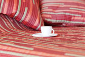 Bed with two pillows, a cup of tea on the blanket — Stock Photo