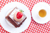 Beau gâteau avec des fraises et de thé sur tissu écossais — Photo