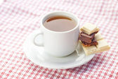 Bar of chocolate and tea on plaid fabric — Foto de Stock
