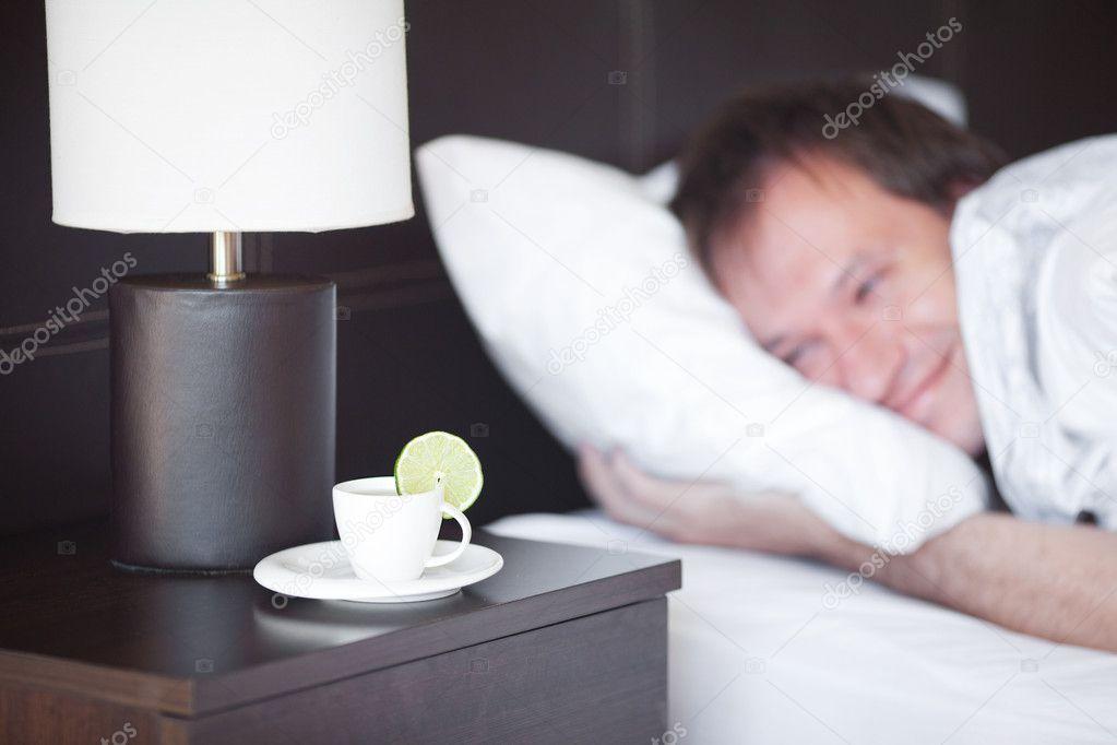 침대, 침대 옆 테이블에 램 차 한 잔에 사람이 자 고 — 스톡 사진 ...