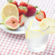 Cocktail with ice,lemon, fig and strawberries on a plate — Foto Stock