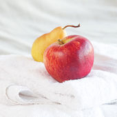 Apple and pear on towels on the bed — Stock Photo