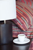 Bed with a pillow, a cup of tea on the bedside table and lamp — Stock Photo