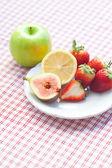 Jablko, citron, fíkovníky a jahody na talíři — Stock fotografie