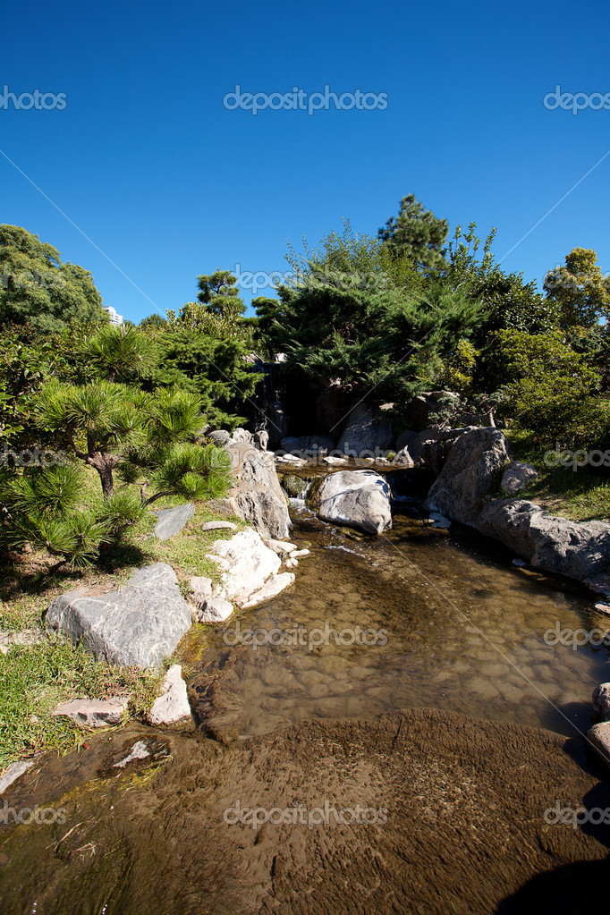 Coniferous trees, rocks and a waterfall on a background of blue sky — Stock Photo #11238014