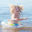 Beautiful little girl splashes in the water — Stock Photo