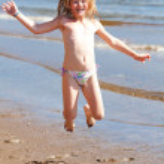 Beautiful little girl jumping on the beach — Stock Photo