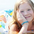 Portrait of a beautiful little girl with a color lifebuoy — Stock Photo