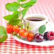 Cup of tea, blackberry,raspberry and rosehip berries with leaves - Stock Photo