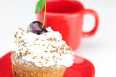 Muffin with whipped cream, cherries and red cup on white backgro — Stock Photo
