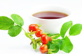 Cup of tea and rosehip berries with leaves on white background — Stock Photo