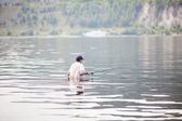 Young man fishing in the river — Stock Photo