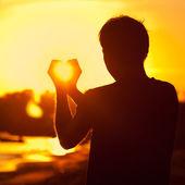 Junger mann hält in händen der untergehenden sonne — Stockfoto