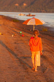 Little girl running along the beach in the sunshine — Stock Photo