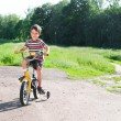 Stock Photo: Little boy riding bike on country road outdoors