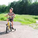 mały chłopiec jazda rowerem na drodze na zewnątrz — Zdjęcie stockowe