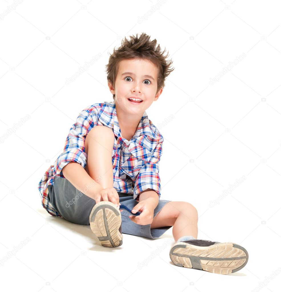 Naughty hairy little boy in shorts and shirt putting on shoes isolated on white — Foto de Stock   #10834731