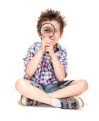 Attentive little boy with weird hair researching using magnifier — Stock Photo