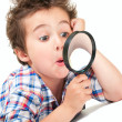 Surprised little boy with weird hair and magnifier — Stock Photo