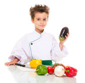 Little boy chef in uniform with knife cooking vegatables holding — Stock Photo