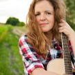 Young redhead woman holding guitar outdoors in summer — Stock Photo