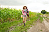 Young redhead woman with guitar passes corn field outdoors in su — Stock Photo