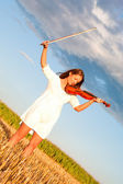 Young woman holding violin and bow outdoors — Stock Photo