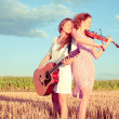 Stock Photo: Two young women playing guitar and violin outdoors. Split toning
