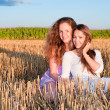 Two girls friends lean each another on summer field — Stock Photo