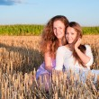 Two girls friends leeach another on summer field — Stock Photo #11921401