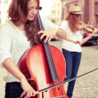 Постер, плакат: Two women strings duet playing violin and cello on the street