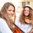 Two women strings duet playing violin and cello on the street - Stock Photo