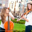 Two women strings duet playing violin and cello in square — Stock Photo