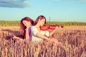 Two young women playing guitar and violin outdoors. Split toning — Stock Photo
