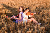 Two young women playing guitar and violin outdoors — Stock Photo