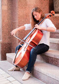 Woman playing cello on the stairway outdoors — Stock Photo
