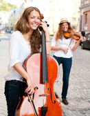 Two women strings duet playing violin and cello on the street — Stock Photo