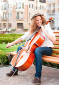 Woman playing cello on the bench in square — Stock Photo