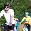 Family on the bike in the sunny forest — Stock Photo