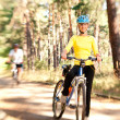 Couple on bikes in the sunny forest — Stock Photo