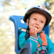 Stock Photo: Little boy in bike child seat eating cracker