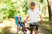 Fathr and little son on bike with child seat — Stock Photo