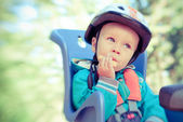 Little boy in bike child seat eating cracker. Cross process — Stock Photo