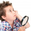 Dreamy little boy with weird hair and magnifier — Stock Photo