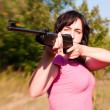 Stock Photo: Womaiming rifle in summer forest. Lensbaby effect