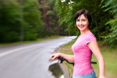 Woman with bike on the rainy forest road. Lensbaby effect — Stock Photo