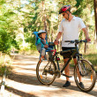 Father and little son on bike with child seat - Stock Photo