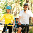 Family on the bike in the sunny forest - Stock Photo