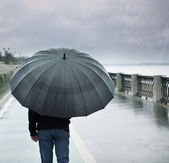 Rain and lonely man with umbrella — Stock Photo